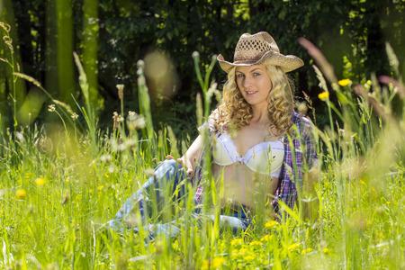 Sexy, blond farmgirl Sittin in een lang voorjaar gras.