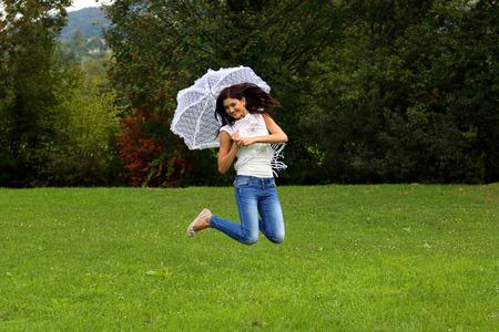 Mooie gelukkige brunette springen met witte kant paraplu.