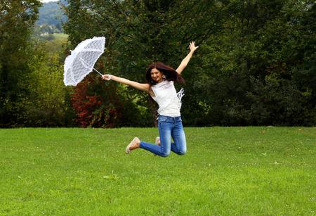 Springende gelukkige vrouw met witte kant paraplu.