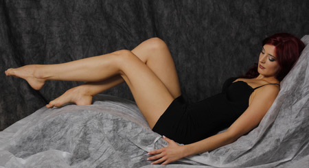 undress: Beautiful red hair woman in black dress and long legs lying down.