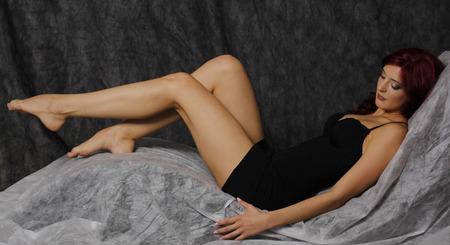 kinky: Beautiful red hair woman in black dress and long legs lying down.