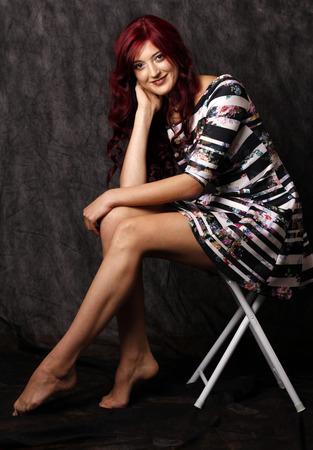 Mooie vrouw met rood haar en lange benen.
