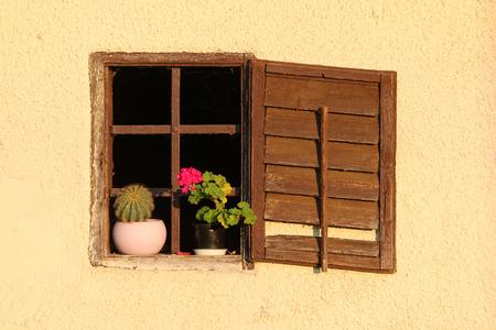 Oud houten venster met sluiter en ijzeren staaf.