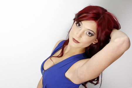 Beautiful sexy redhead posing in blue dress.