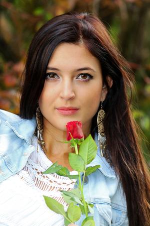 Mooie brunnette met rode roos. Stockfoto