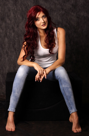 Beautiful woman with red hair posing in studio. Stock Photo