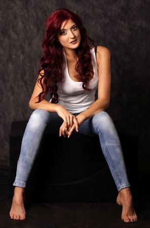 modelos posando: Mujer hermosa con el pelo rojo que presenta en estudio. Foto de archivo