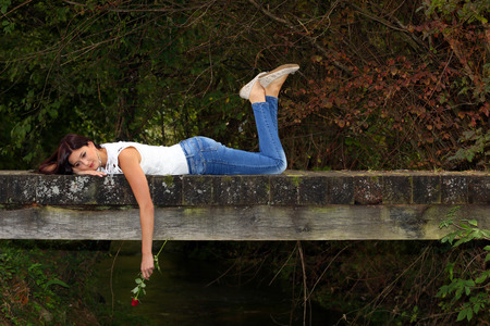 Beautiful woman lying on the wooden bridge in the park with red rose in her hand. Standard-Bild