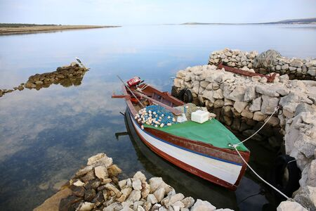 Small, old fishing boat at the dock in the island of Pag, Croatia.