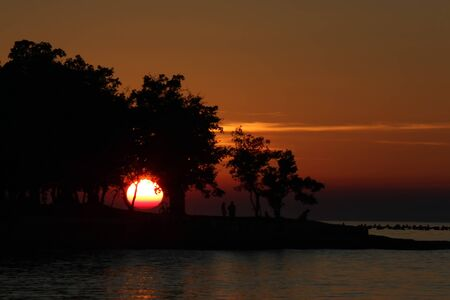 Orange sunset over the Adriatic sea and beach in Croatia with silhouette of the people.