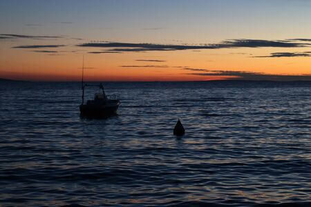 Orange sunset over the Adriatic sea in Croatia with small boat.