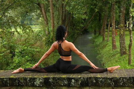 Beautiful girl doing a yoga pose on the small wooden bridge in the park. Standard-Bild