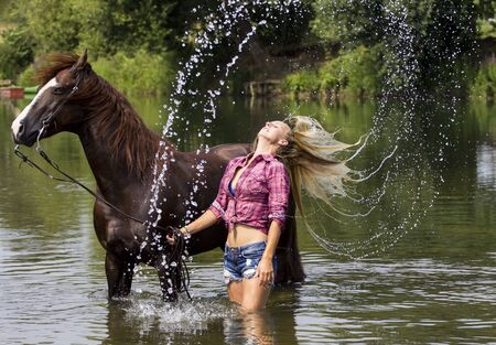 Beautifu, sexyl blonde cowgirl with her horse in the water.