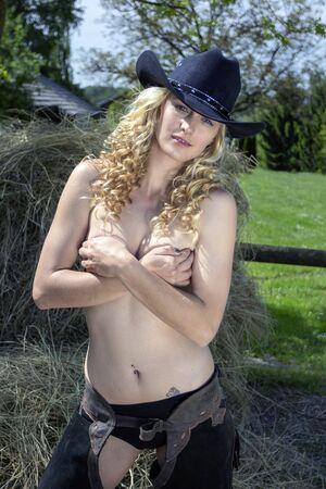 Sexy blonde cowgirl with cowboy hat standing in hay. Standard-Bild