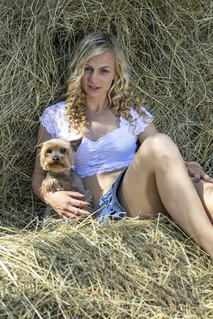 Young, blond woman lying in a hay with her small dog. Standard-Bild