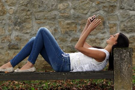 Smiling woman lying on the bench and using smartphone.