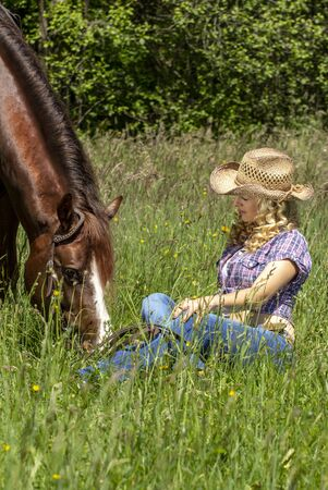 Beautiful blonde cowgirl sitting in the grass with her horse.