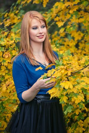 Young woman with long red hair relaxing in the autumn park. Standard-Bild