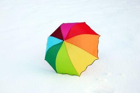 Rainbow colorful umbrella in the fresh snow. Standard-Bild