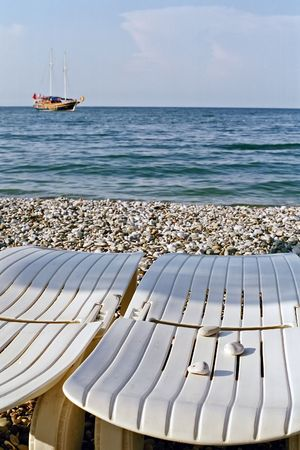 three stones on white chaiselongue on a pebble beach photo