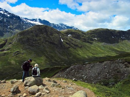 Man and woman have a rest among mountains. Jotunheimen national park, Norway