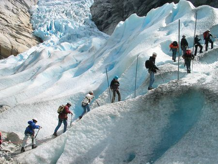 Group of tourists is climbing to a glacier. Briksdal glacier,Jostedalsbreen national park, Norway.