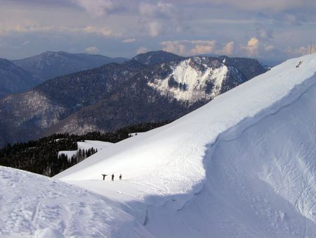 boarders: three persons climb down a mountain on foot. Red Field, Caucasia, Russia Stock Photo