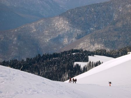 boarders: group of skiers and boarders is climbing a mountain. Red Field, Caucasia, Russia. Stock Photo