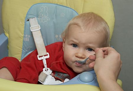 amusing: amusing baby with a spoon in a mouth