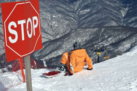 wintersport: snowborder sitting under stop-sign Stock Photo