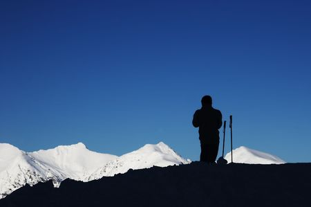 eminence: black silhouette of skier, blue sky and white mountain Stock Photo