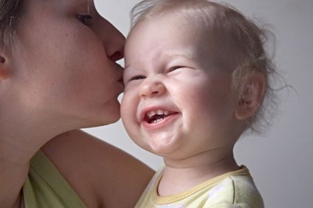 with fondness: mother kissing baby