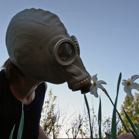 gasmask: woman smelling flower in gas-mask
