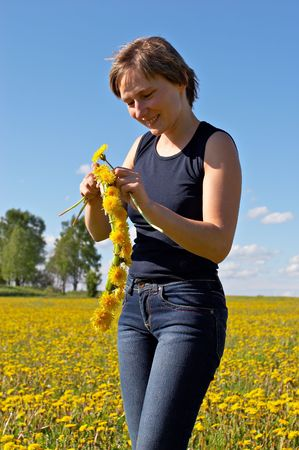 young woman twining a dandelion wreath on a beautiful meadow photo