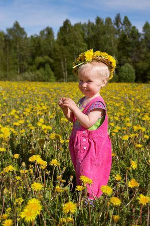 cute girl in flower wreath on a beautiful meadow photo