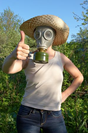 gasmask: woman in gas-mask on garden background with all right sign of hand