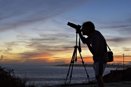 silhouette of the photographer with camera and tripod. Stock Photo - 586621