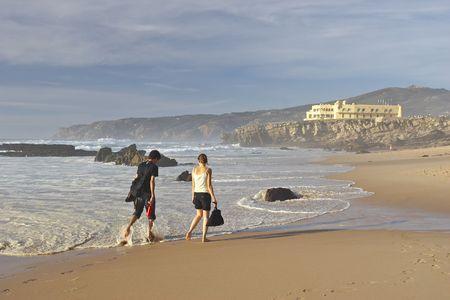 young man and woman walking along ocean photo