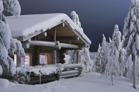 wooden cottage in the forest covered by snow