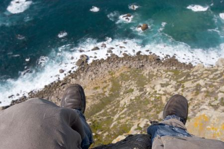 cliff edge: feet of man sitting on the very edge of high rock above the sea Stock Photo
