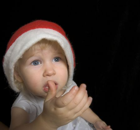 pitiful: pitiful little girl in christmas santa hat, isolated on black Stock Photo