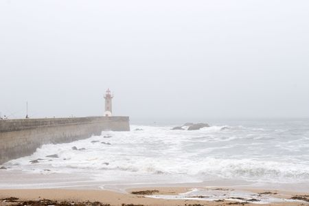 lighthouse on pier in haze and ocean waves, Porto, Portugal photo
