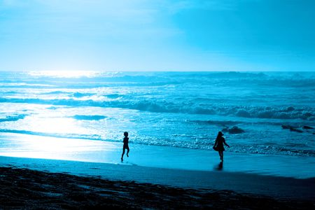couple lit: Ni�os corriendo en la noche en la playa del oc�ano azul  Foto de archivo