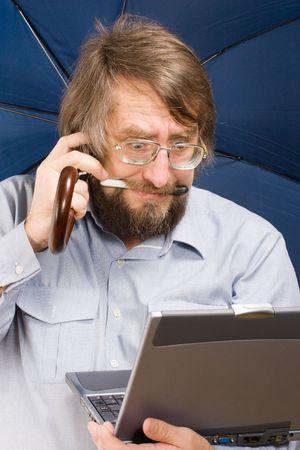 businessman with very surprised face in glasses with notebook, phone mobile, umbrella in his hands and pen in his teeth photo
