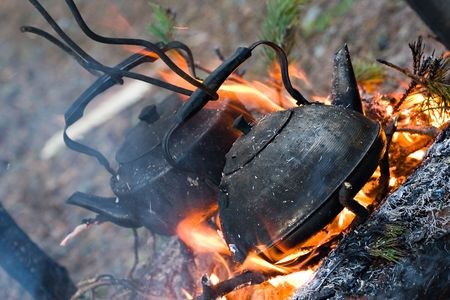 two old sooty kettles with boiling water above campfire photo
