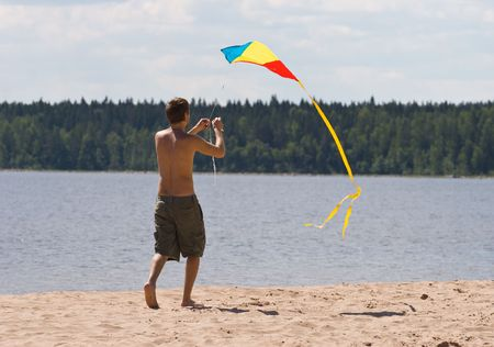young man flying kite on a lake beach photo