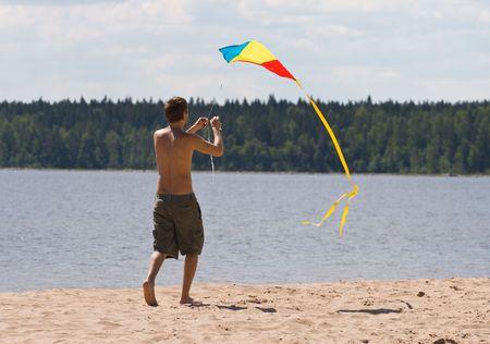lake beach: young man flying kite on a lake beach
