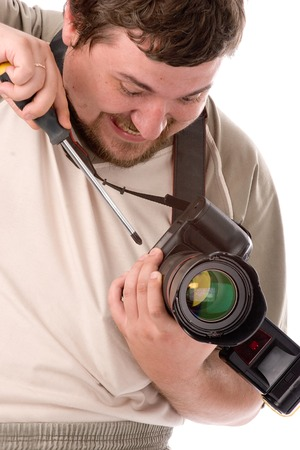 man with terrible facial expression and big screwdriver in hands fixing new DSLR camera photo