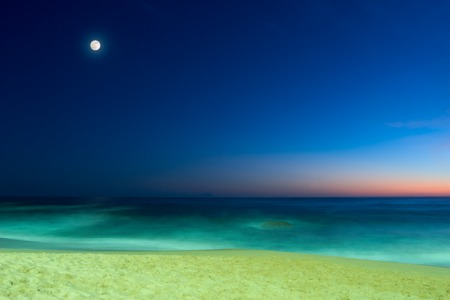 evening seascape with sandy beach, calm ocean and full moon on blue sunset sky  Stock Photo - 1702302
