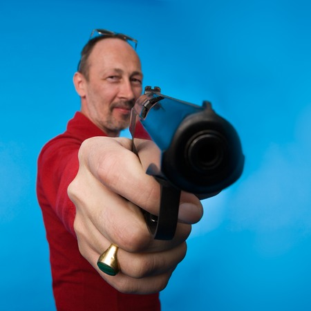 point and shoot: Sonriendo g�ngster y la celebraci�n de una pistola apuntando a la c�mara
